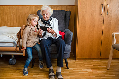 Aged woman watching together with her great-granddaughter photos on smartphone - p300m2069623 by Petra Silie