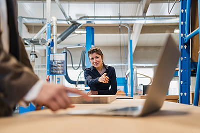 Businesswoman pointing at laptop while working with colleague in industry - p300m2250795 by Daniel Ingold