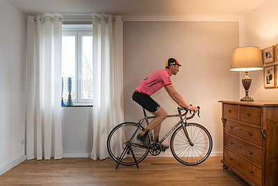 Man on racing bike in his apartment - p305m1586711 by Dirk Morla