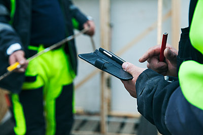 Mid-section of construction worker opening note pad - p312m1107641f by Lena Koller