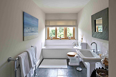 Square framed mirror and artwork hang in bathroom of Canterbury home - p349m790937 by Polly Eltes