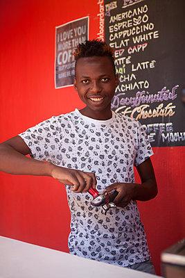 Freundlicher Barista presst Kaffeepulver in den Filter - p045m1444511 von Jasmin Sander