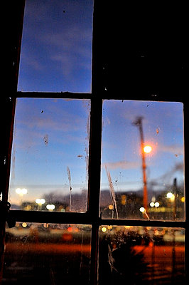 View through warehouse building window at night - p1047m789464 by Sally Mundy