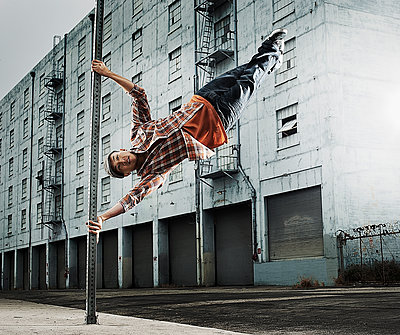A young man breakdancing, leaping in the air, and stretching out.  - p1100m1107163 by Mint Images
