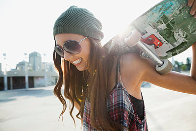 Teenage girl with skateboard - p1192m1014250f by Hero Images