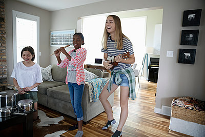 Tween girl friends playing musical instruments in living room - p1192m2009614 by Hero Images