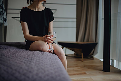 Woman with a glass siting on a bed - p1414m2044883 by Dasha Pears