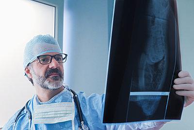 Hispanic surgeon examining x-ray - p555m1232015 by REB Images