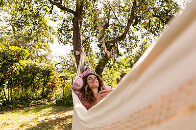 Young woman relaxing in hammock - p788m2031154 by Lisa Krechting