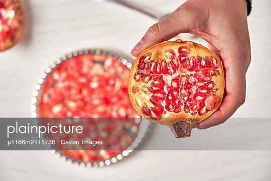 Hands Holding The Pomegranate Fruit And Using Spoon To Pick The Seeds - p1166m2111736 by Cavan Images