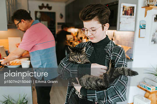 Girl carries cat in her arms at home - p1507m2150441 by Emma Grann