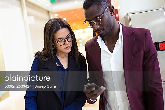 plainpicture - plainpicture p300m2083424 - Business people checking sm... - DEEPOL by plainpicture/Josep Suria