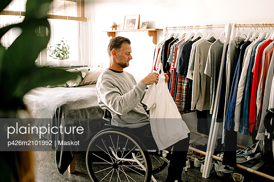 Side view of disabled mature man holding white t-shirt while sitting on wheelchair by clothes rack at home - p426m2101992 by Maskot
