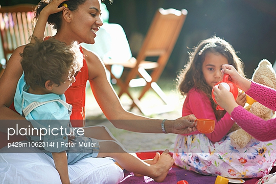 Mother and children playing picnics at garden birthday party