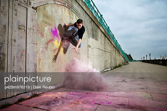 Parkour athlete experimenting with movement and powder paint at Balcombe Viaducts, Sussex, United Kingdom