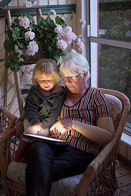 Grandmother with granddaughter using digital tablet - p312m1103886f by Benny Karlsson