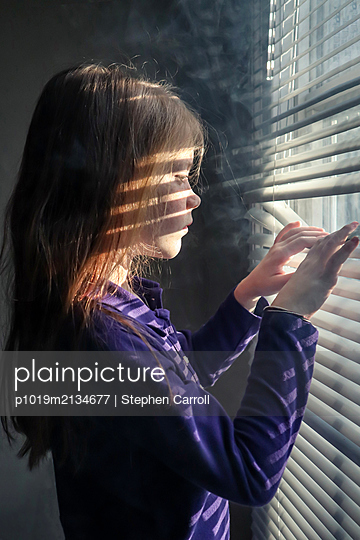 Girl looks through blinds at the window - p1019m2134677 by Stephen Carroll