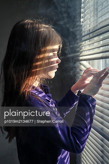 Mädchen blickt durch die Jalousie am Fenster - p1019m2134677 von Stephen Carroll