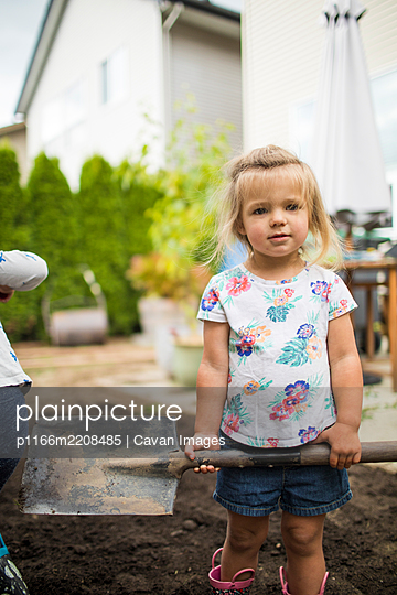 Portrait of cute blonde two-year-old helping dad with shoveling dirt. - p1166m2208485 by Cavan Images