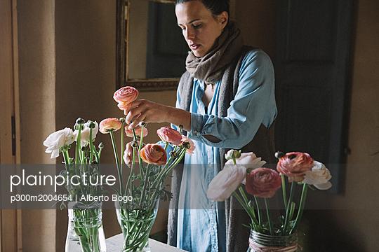Woman arranging fresh flowers - p300m2004654 von Alberto Bogo