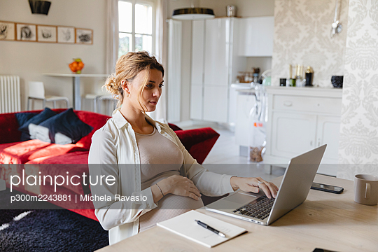 Pregnant businesswoman working on laptop at desk at home - p300m2243881 by Michela Ravasio