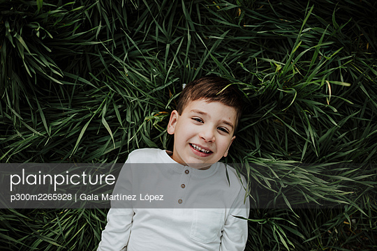 Boy smiling while lying on grass - p300m2265928 by Gala Martínez López