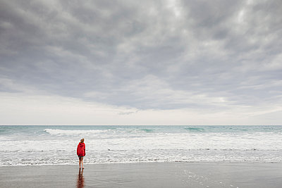 Young girl standing at the edge of the water at the beach - p1166m2113566 by Cavan Images