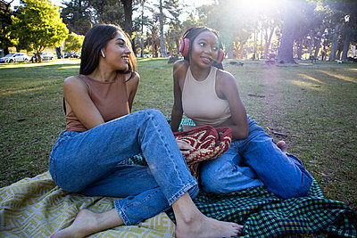 Two teenage girls with earphones listen to music in the park - p1640m2259875 by Holly & John