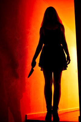 Woman holding knife against red light - p1695m2290938 by Dusica Paripovic