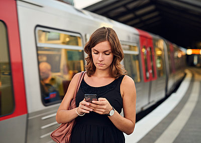 Germany, Young woman with smart phone exploring Hamburg - p300m1191702 by Willing-Holtz