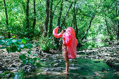 Woman walking in river, carrying an inflatable flamingo - p300m2042148 by Kiko Jimenez