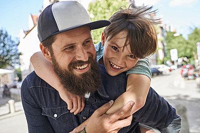 Playful son arm around father on street - p300m2287596 by Stefanie Aumiller