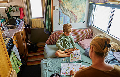 Mother and son cutting out pictures in campervan, Chuquisaca, Bolivia, South America - p429m1519628 by Stephen Lux