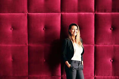 Young woman against burgundy button-tufted wall panels - p429m2091236 by Diego Cervo