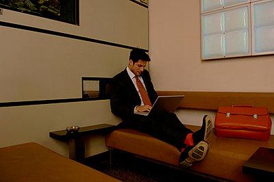 Geschäftsmann benützt Notebook in einem Wartezimmer - p4901799 von Stock4B
