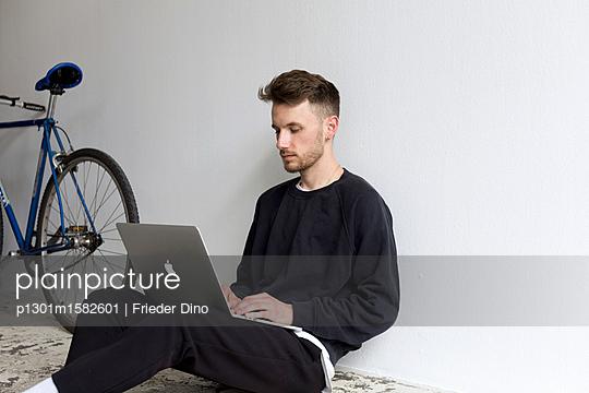 Junger Mann mit Laptop Computer sitzt auf dem Fußboden - p1301m1582601 von Delia Baum