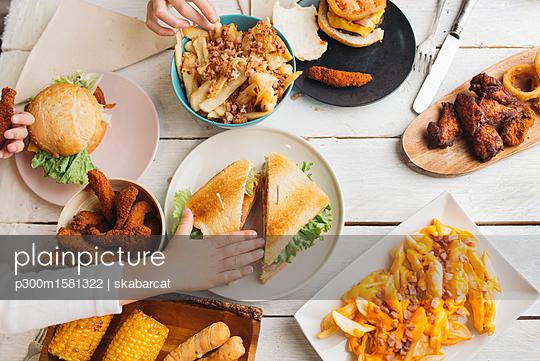Children's hands on table full of American food - p300m1581322 von skabarcat