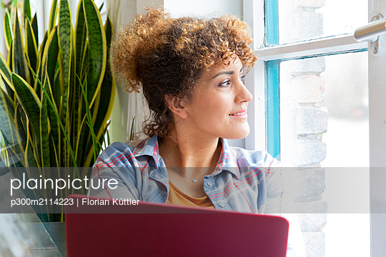 Woman with laptop looking out of window in office - p300m2114223 by Florian Küttler