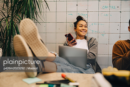 Smiling young businesswoman sitting with feet up on desk using wireless technologies by colleague against wall at office - p426m2023292 by Maskot