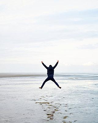 Mann springt im Watt - p1124m1015288 von Willing-Holtz