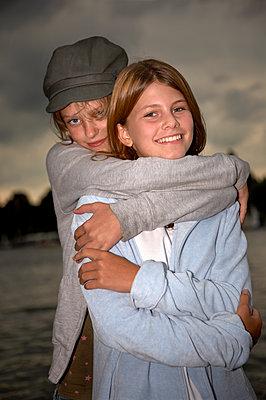 Zwei Freundinnen umarmen sich - p1207m1111702 von Michael Heissner