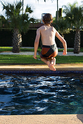 Junge springt in Pool - p635m1042188 von Julia Kuskin