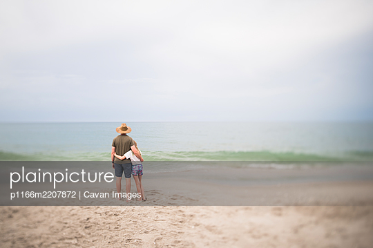 Man and Young Girl Standing Looking Out at the Ocean in Indialantic FL - p1166m2207872 by Cavan Images