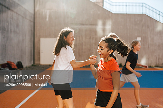 Happy female friends holding hands while playing in basketball court - p426m2298569 by Maskot