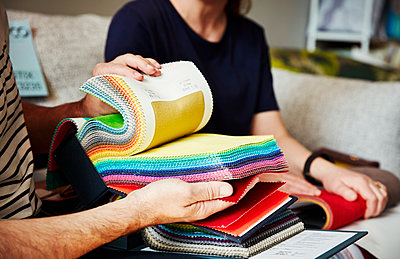 Two people sitting on a sofa, looking at a selection of fabric samples. - p1100m1177685 by Mint Images