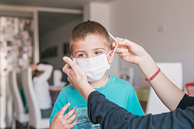 mother putting medical mask on her son to protect himself from the coronavirus - p1166m2182900 by Cavan Images