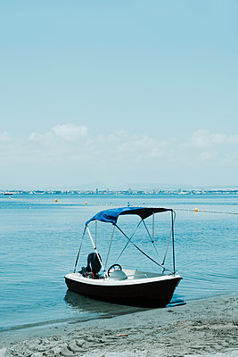 Boat moored on the sand of the shore of a lake, a bay or a beach - p1423m2289766 by JUAN MOYANO