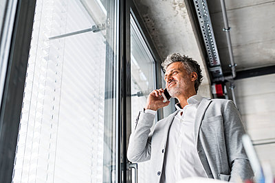 Smiling mature businessman on cell phone at the window in office - p300m1535963 by HalfPoint