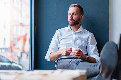 Businessman in office having a coffee break - p300m2131820 by Daniel Ingold