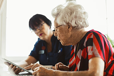 Senior woman using digital tablet with caretaker at home - p426m1468267 by Maskot